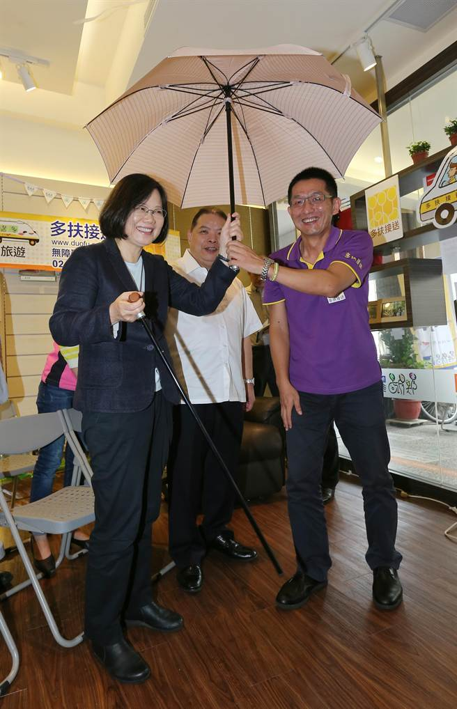 蔡英文(左)在多扶接送執行長許佐夫(右)的教學下,體驗「藏杖傘」的便利通用設計。(黃世麒攝)