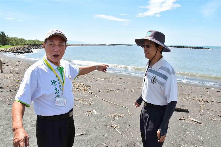 東港鎮長徐志雄(左)指出,迎王場地受浪濤大面積掏空。(許智鈞攝)