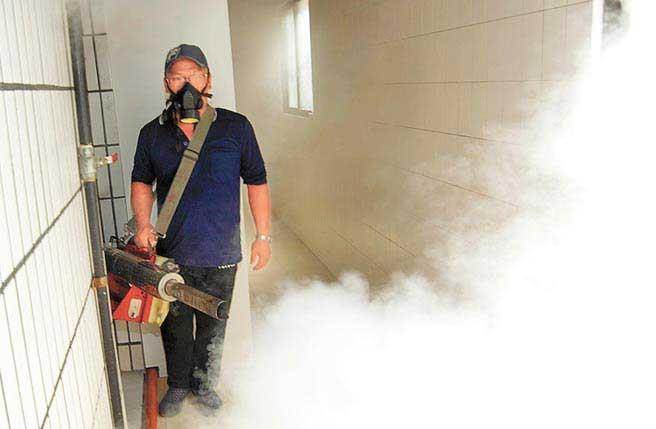 防疫人員正在進行登革熱消毒工作。(本報系資料照片)