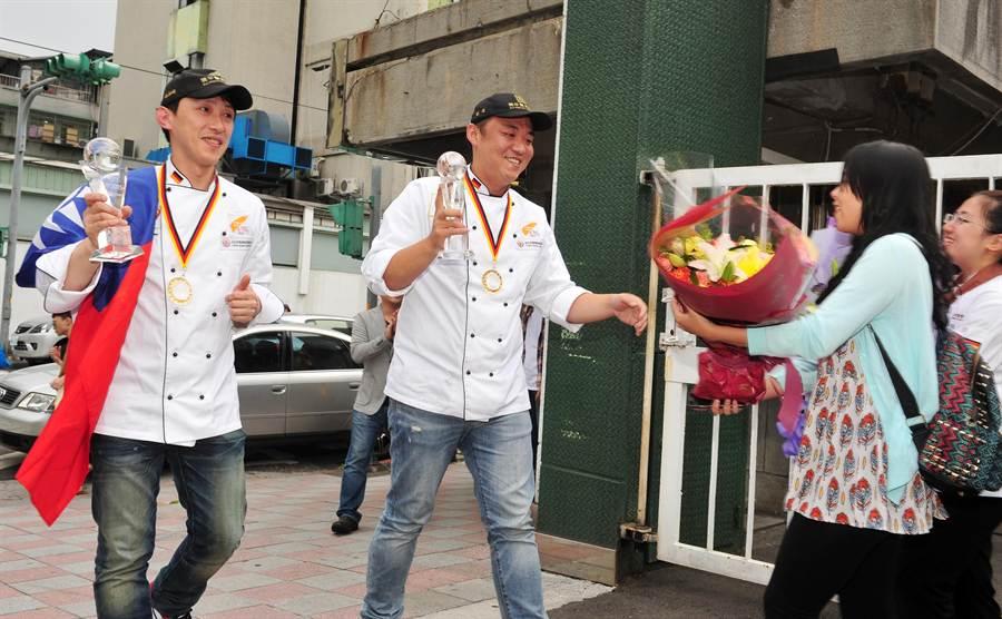 彭浩(右)、楊嘉明(左)拿著獎盃踏進校園,受到同學們獻花、尖叫熱烈迎接。(劉宗龍攝)