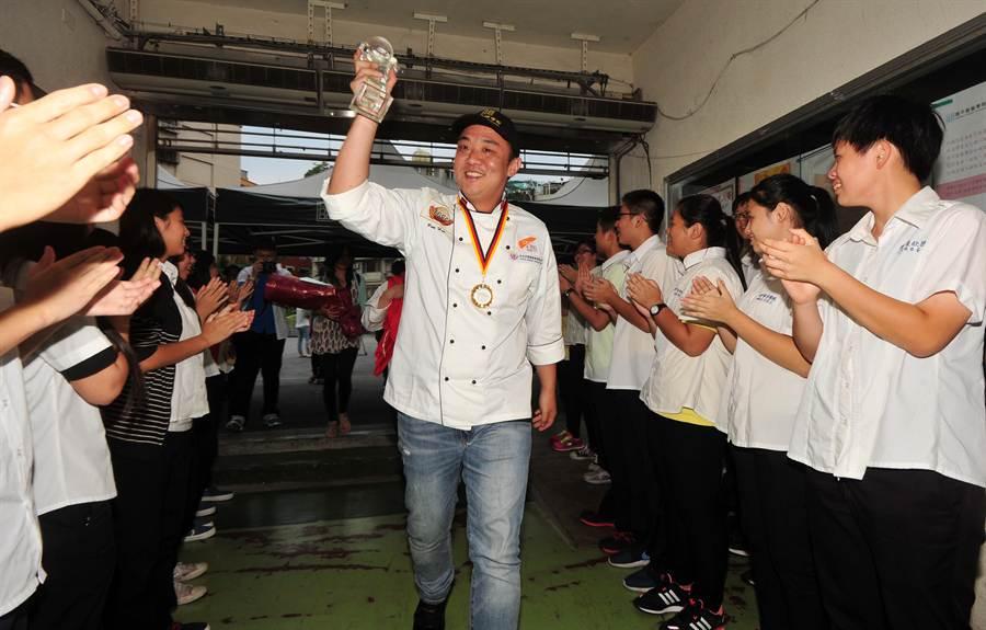 奪下IBA世界西點大賽金牌,載譽返國的彭浩(中)走進歡迎會場時,同學們夾道鼓掌迎接。(劉宗龍攝)