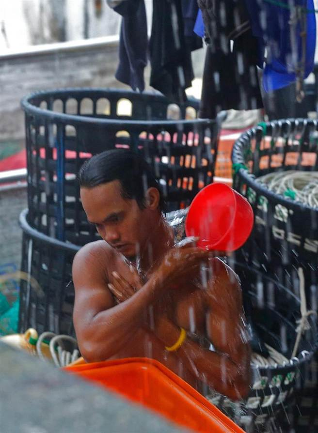 杜鵑強颱將來襲,外籍漁工在雨勢中趁空閒洗澡。(方濬哲攝)