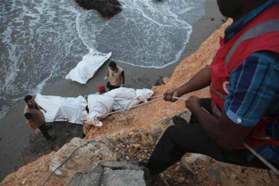 紅新月會人員在利比亞岸邊將偷渡者屍體拉上岸。(美聯社)