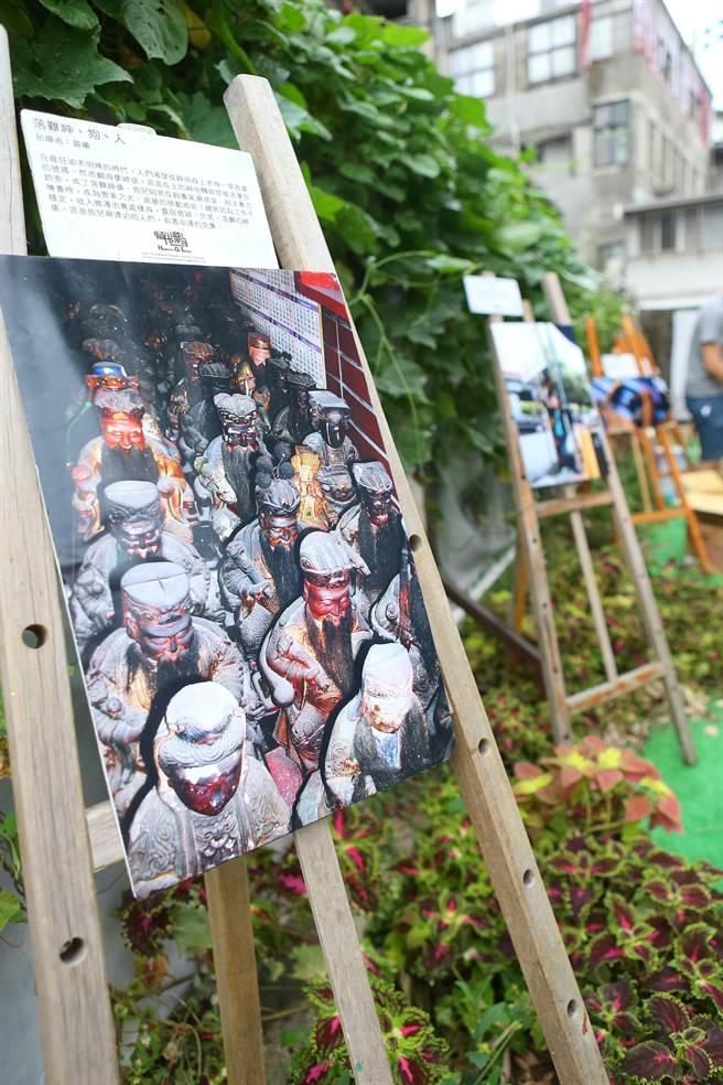 關心街友的「人生百味」在10日世界街友日舉辦「食宴性質」的活動,台灣當代漂泊協會在現場陳列街友們拍攝的照片,其中這個作品叫「落難神、狗、人」,表達出街友與落難神像有相似的處境。(余祥攝)