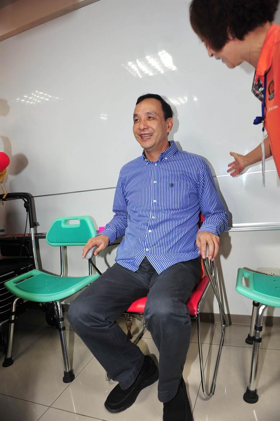 新北市長朱立倫(左)16日出席「新北市社會企業發展中心」開幕茶會,參觀新北市銀髮族協會的攤位及試坐適合老人坐的椅子產品。(劉宗龍攝)