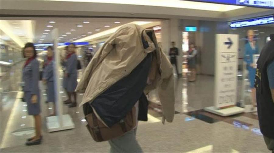 在班機上分娩的簡姓婦人遭美遣返出境,她用米色外套蓋住頭部,不願回應任何問題。(翻攝自快點TV)