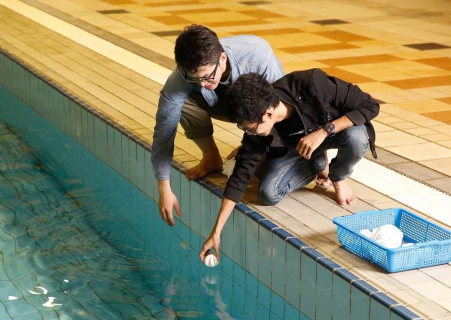 中華大學工程系學生(左起)蔡輝煌、黃暐倫,將共同研發、有效解決優養化的Green Fairy,置於游泳池中試驗。(郭芝函攝)
