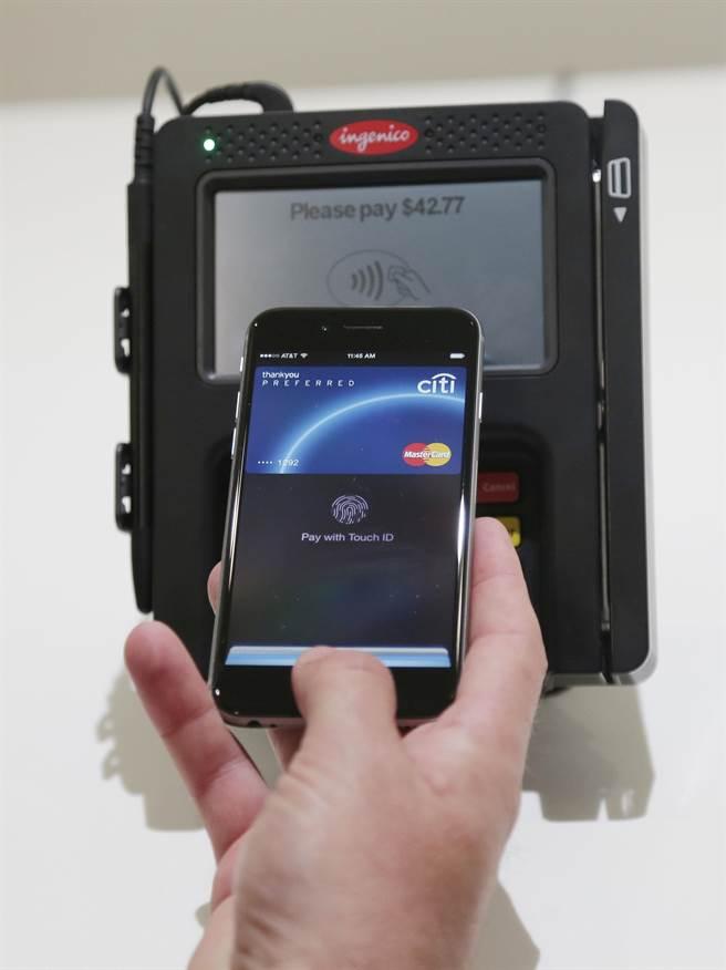 蘋果去年10月在公司總部展示蘋果支付(Apple Pay)的功能,用手機在支付掃瞄器上一刷就能完成支付,對蘋果迷而言相當有吸引力。(檔案照片/美聯社)