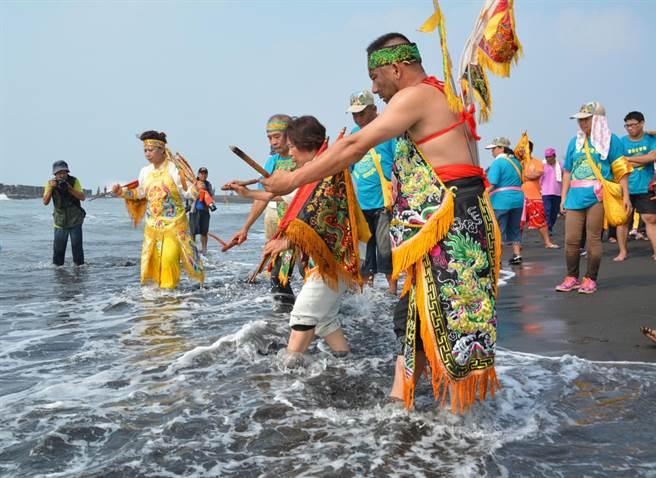 待請神安營法會結束,各轎班人員紛紛入海請水。(周綾昀攝)