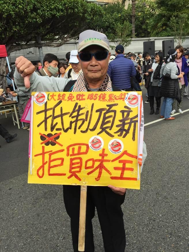 68歲王溪河自製標語,抗議頂新食品。(廖珮妤攝)