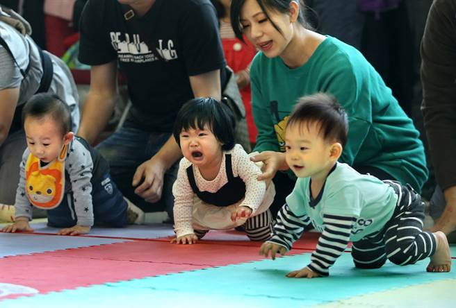 1位小妹妹在寶寶爬行賽中哭了出來,身旁家人予以安撫,現場笑聲不斷。(王錦河攝)