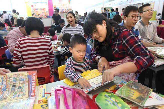 家長帶小朋友在兒童益智遊戲教材區體驗。(王錦河攝)