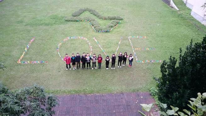 同學拿著五彩的小風車在綠色草地上組成大大的LOVE地景。(葉書宏翻攝)
