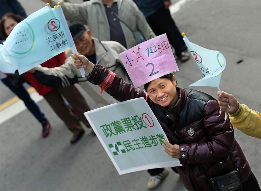 1位自製小英加油看板綁在頭上的女子和眾人在路口揮旗力挺。(王錦河攝)