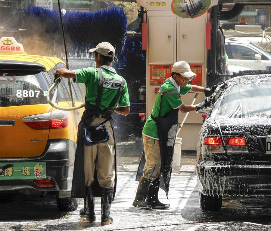 過年期間汽車洗車、打蠟也紛漲。圖為加油站洗車工人。(本報系資料照)