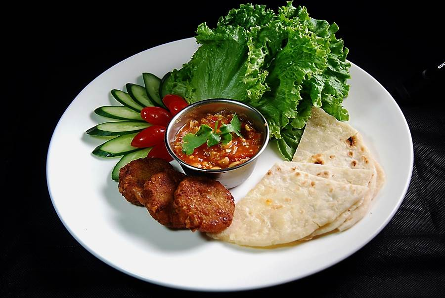 〈泰北沙拉〉的豆餅是用有機黃豆作的,手工印度餅皮則是用印度酥油和麵粉作的,提味的醬料則是用泰式醬汁、牛番茄、洋蔥酥、花生、洋蔥和檸檬葉,以及香菜梗熬製。(圖/姚舜攝)
