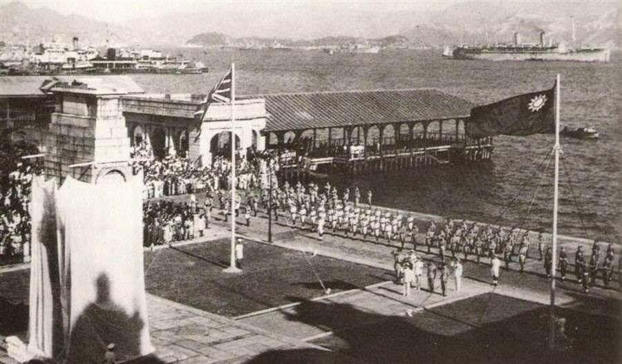 1945年9月,盟軍在香港中環勝利紀念碑前舉行勝利遊行,圖中可見代表中華民國的青天白日滿地紅國旗。(網路照片)