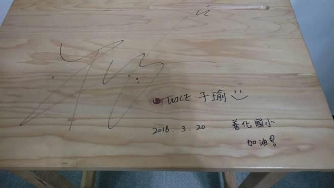 周子瑜今日返台參加國中學力同等鑑定,有志工要求她在課桌椅上簽名留念。(莊曜聰攝)