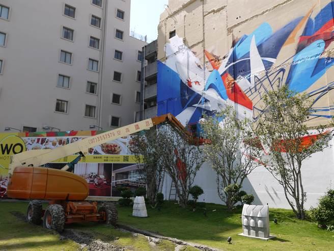 藝術家們21日搭上吊車分別在前金國中、國小、幼稚園、區公所和HOTEL WO旁外牆,創作巨幅塗鴉彩繪。(劉宥廷攝)