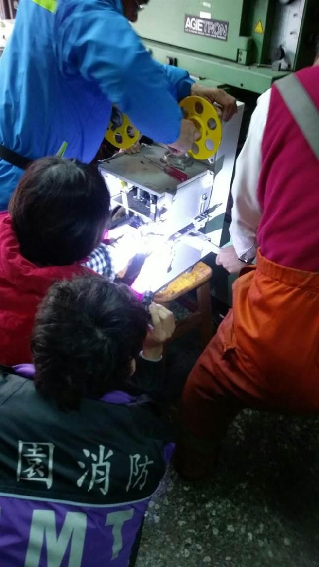 桃園市龍潭區中興路1名2歲幼童遊玩時,將手掌深入飲料封口機,遭卡住,消防隊員趕緊協助救援。(賴佑維翻攝)