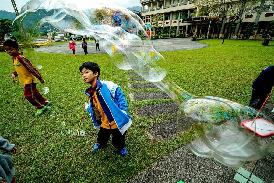 員山鄉大湖國小邀請童玩推廣老師,讓校園變成遊戲場,學生用鐵絲製成的工具沾泡泡水後,拉出巨大的泡泡。(李忠一攝)