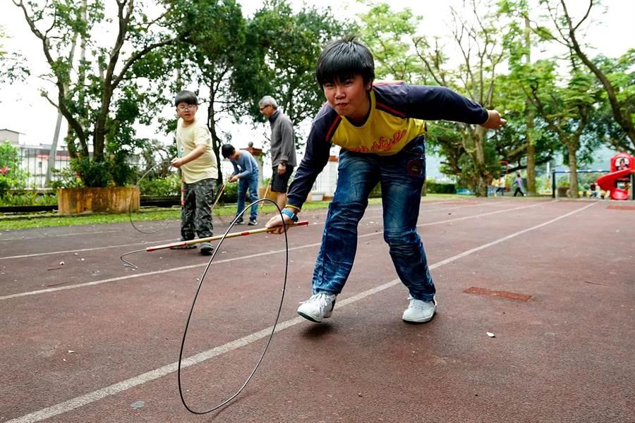 大湖國小學生體驗滾鐵環遊戲。(李忠一攝)