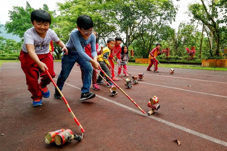 在跑道上的學生們,玩著鐵罐做成的「玲瓏車」比誰速度快。(李忠一攝)