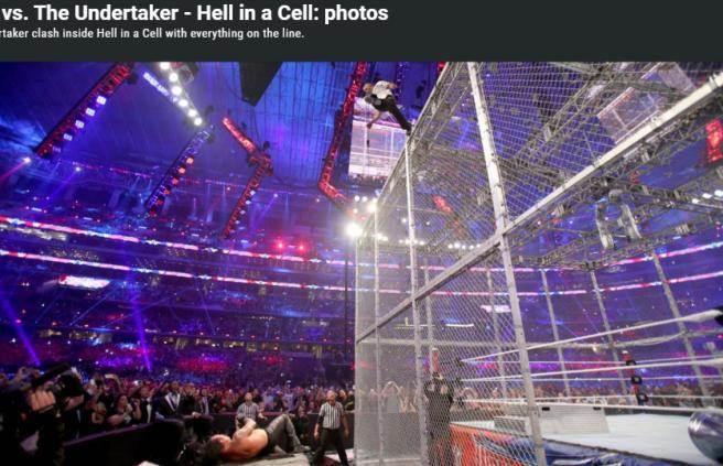 辛恩(上)從20呎高的鐵籠頂一躍而下,攻擊躺在播報台上的送葬者。(取自WWE官網)