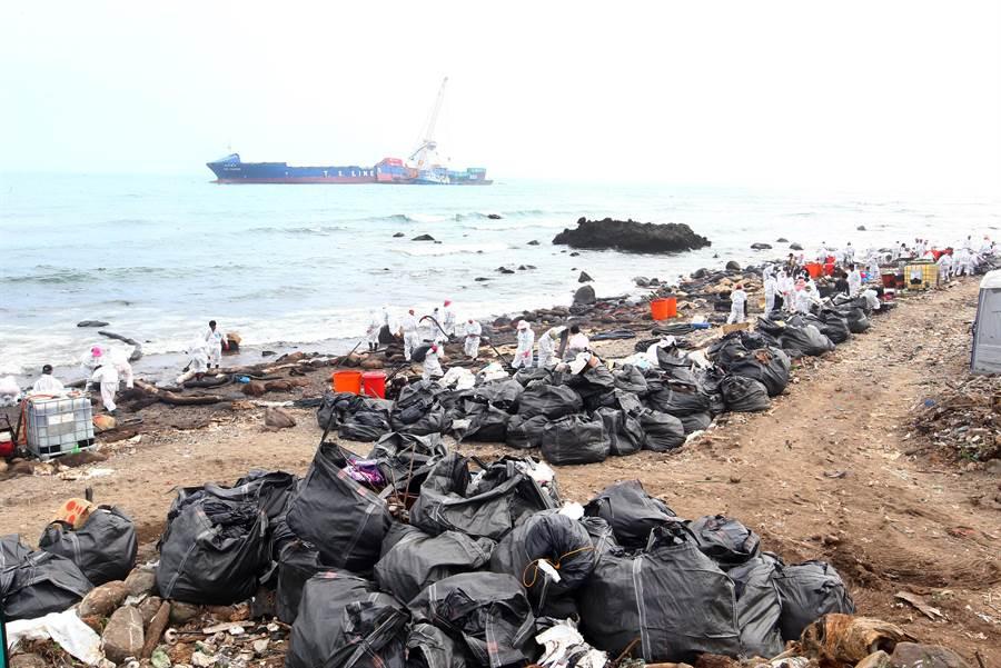 「德翔台北」貨櫃船擱淺新北市石門海岸,造成船身斷裂,重油外洩污染北海岸,工作人員持續與清理石門岸邊油污,清理油污後也造成許多廢棄物,堆滿岸邊。(陳信翰攝)