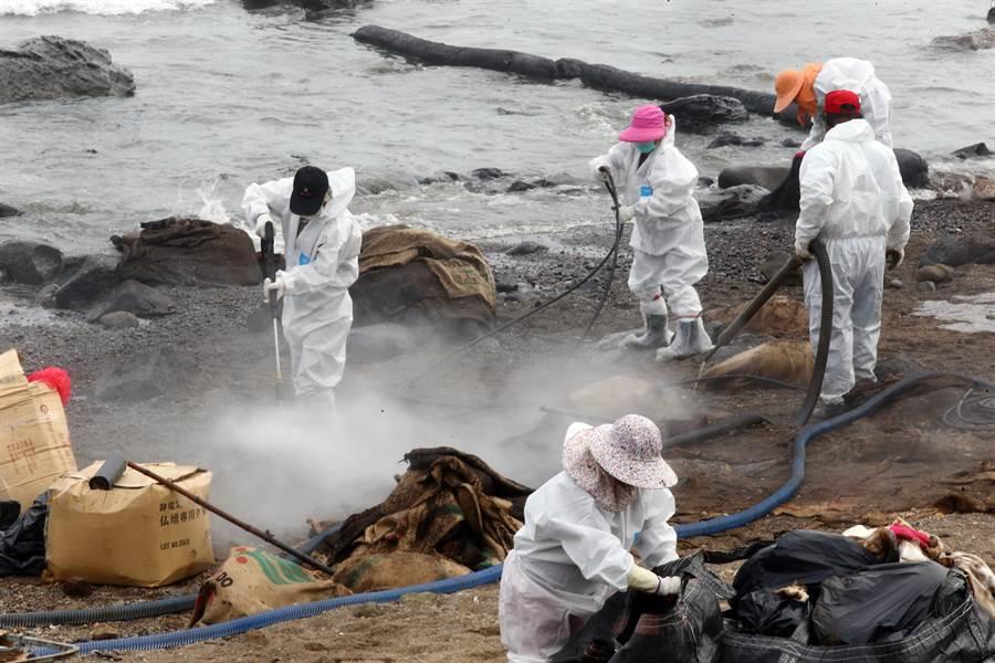 工作人員持續與清理石門岸邊油污。(陳信翰攝)