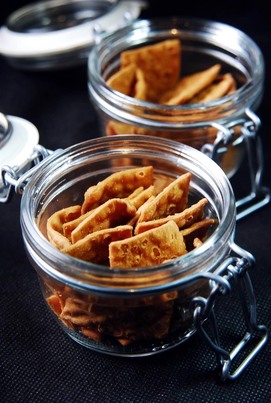 〈黑輪吧〉的客人在等待廚師煮黑輪時,可以免費吃台南的〈菜脯餅〉。(圖/姚舜攝)