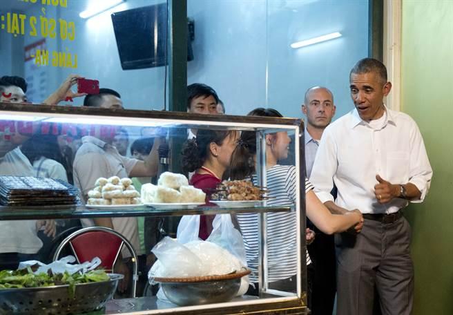 吃飽喝足的歐巴馬走出河內小吃店,快樂地向店家和民眾打招呼畫面。(圖取自美聯社)