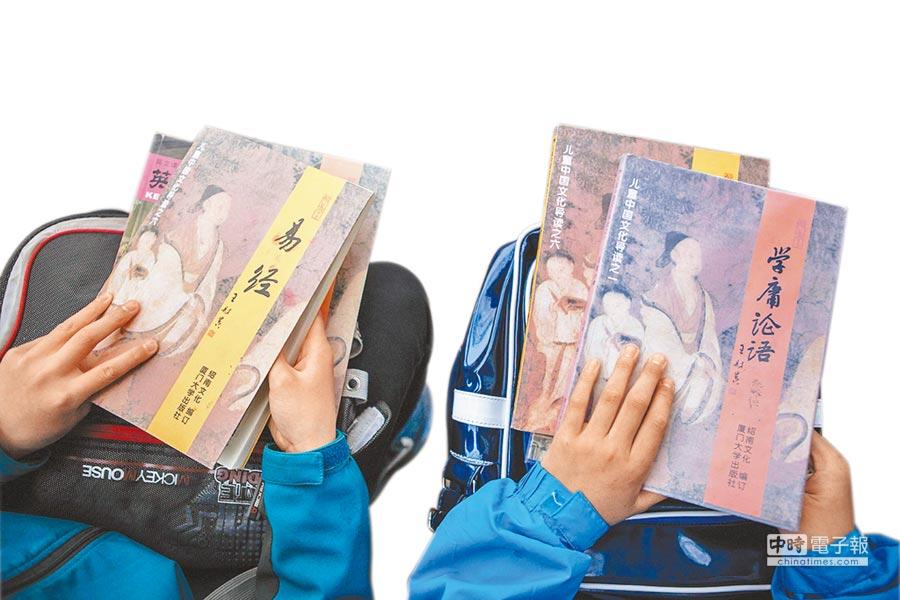銀川市兩位國一學生等候公車時,閱讀《易經》和《學庸論語》。(新華社資料照片)