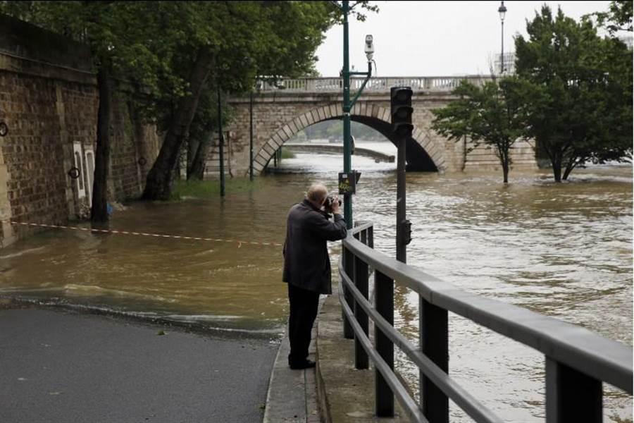 趁著雨勢稍緩,不少巴黎居民駐足在塞納河邊,看到平日的河流變得波濤洶湧,或拿出相機拍下百年難得一見的景象。(美聯社)