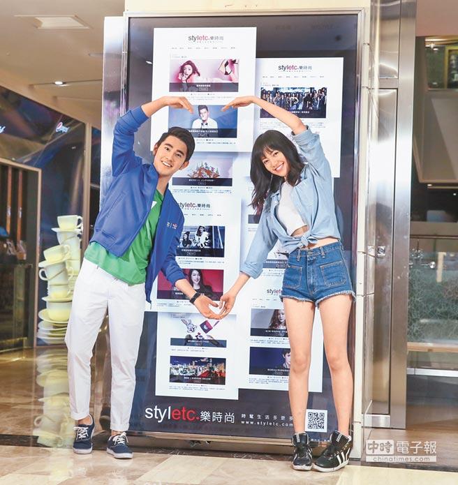 焦曼婷(右)和馬曉豪號召粉絲關注「樂時尚styletc.com」,兩人在看板前比愛心。(盧禕祺攝)