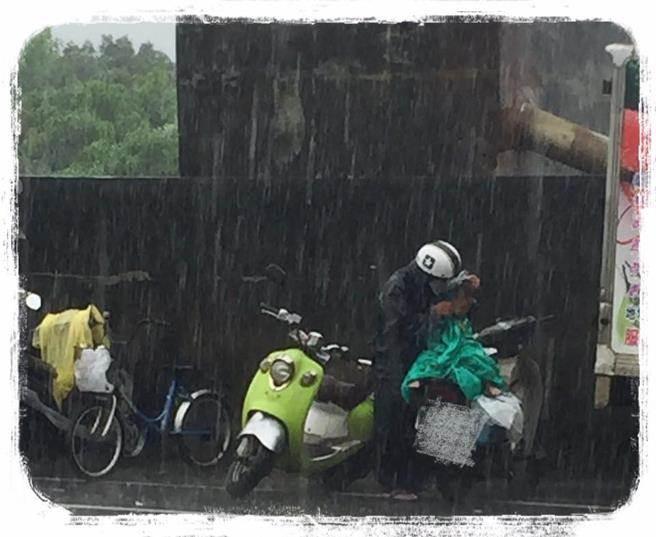 爺爺在大雨中帶著孫子等食餘,這一幕讓很多網友心碎。(翻攝自網友臉書)