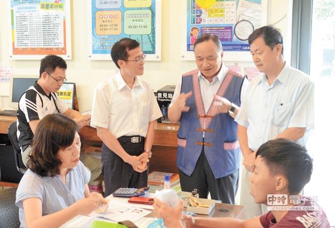 東辦執行長許傳盛(後右)與台東縣政府秘書長陳明仁(後中),昨天視察了解行動領務業務。(黃力勉攝)