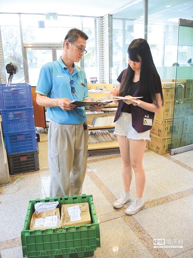 讀者寄回的書本包裹由北市圖館員逐一打開,辦理還書手續。(張潼攝)