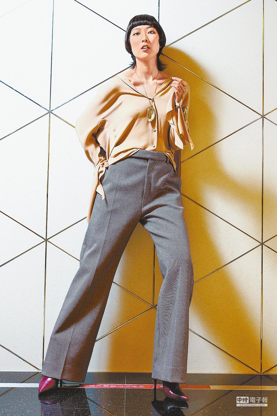 BALENCIAGA早秋服飾更為實穿,裸色方巾襯衫5萬1400元、格紋寬褲2萬9900元、貝殼項鍊、手環價格未定。(鄧博仁攝)