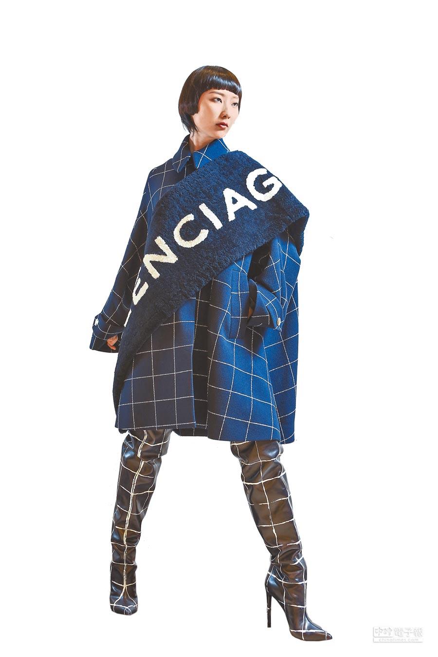 BALENCIAGA早秋將衣服標籤放大,成為羊毛圍巾,藍色格紋大衣與羊毛圍巾皆8萬5900元、格紋長靴5萬7900元。(鄧博仁攝)