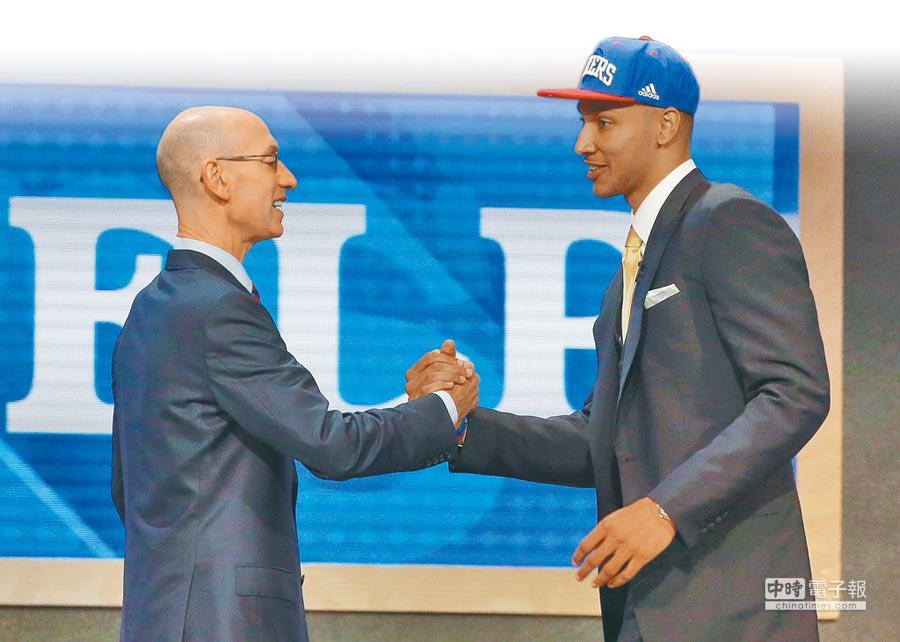 西蒙斯(右)被費城七六人隊在首輪第1順位選中,成了「選秀狀元」,左為NBA總裁席爾佛。(美聯社)