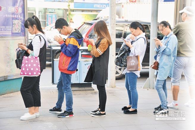 5月20日,瀋陽公車站前等車民眾,低頭看手機打發時間。(CFP)