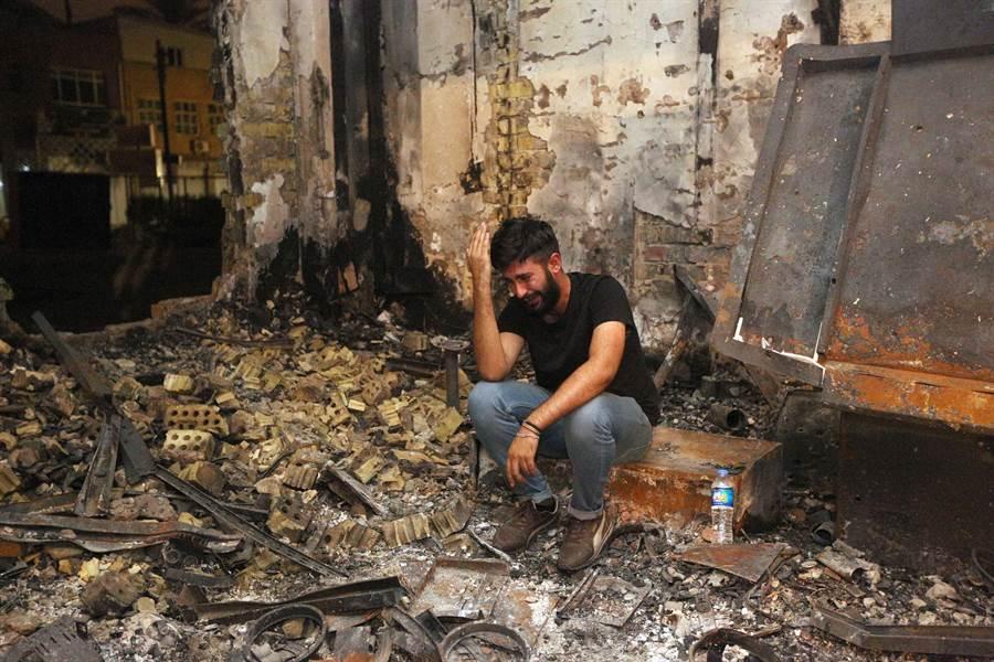 政府官員貪瀆,民眾付出的是血淋淋的代價。多年來,伊拉克以偽造炸彈探測器維護民眾安全,讓恐怖組織IS有機可乘。圖為一名男子4日在巴格達卡拉達區炸彈攻擊現場,為喪生的手足痛哭失聲。(圖/美聯社)