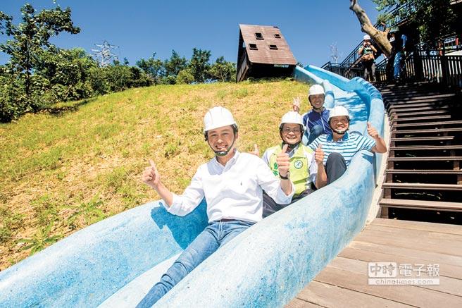 新竹市長林智堅(左)15日到青青草原探勘磨石子溜滑梯,現場試溜一段。(徐養齡攝)