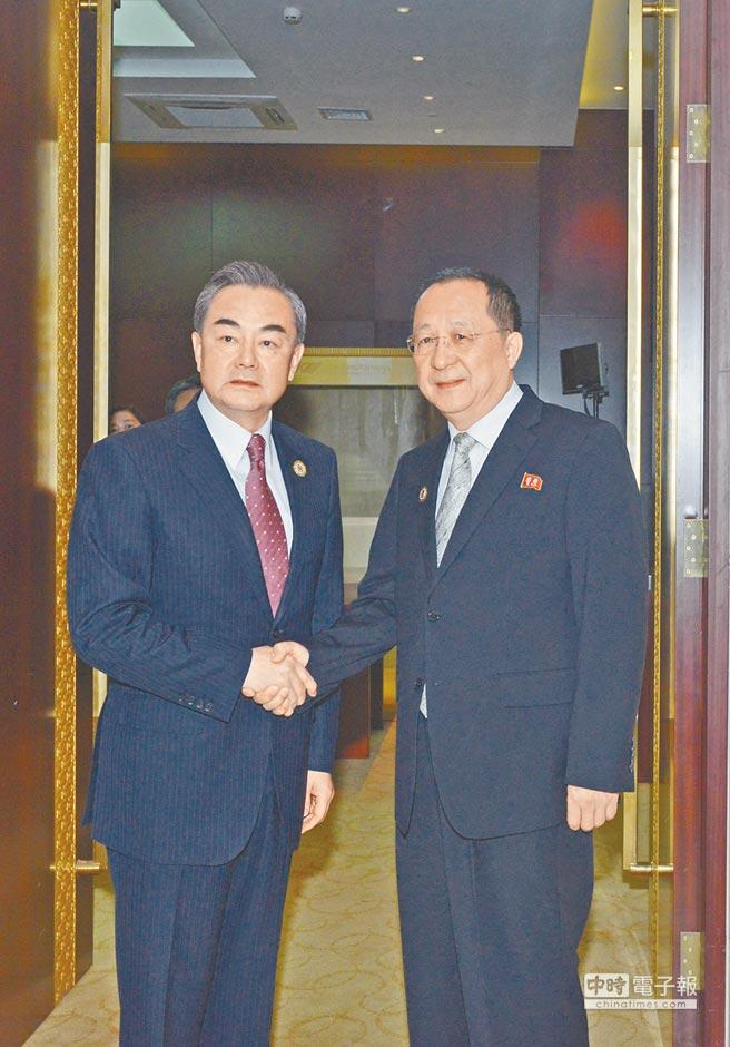 大陆外交部长王毅(左)25日在寮国会见北韩外长李勇浩(右)。(新华社)