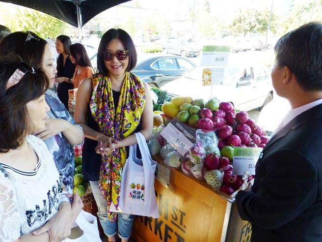 旅居溫哥華的崔麗心(中)邀當地友人參加高雄水果拓銷活動。(高市農業局提供)