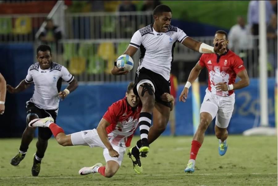 斐濟(白球衣)在7人制橄欖球賽男子組金牌戰遇上過去的「殖民祖國」英國,結果以43比7大勝,贏得該國歷史上首面奧運金牌。(美聯社)