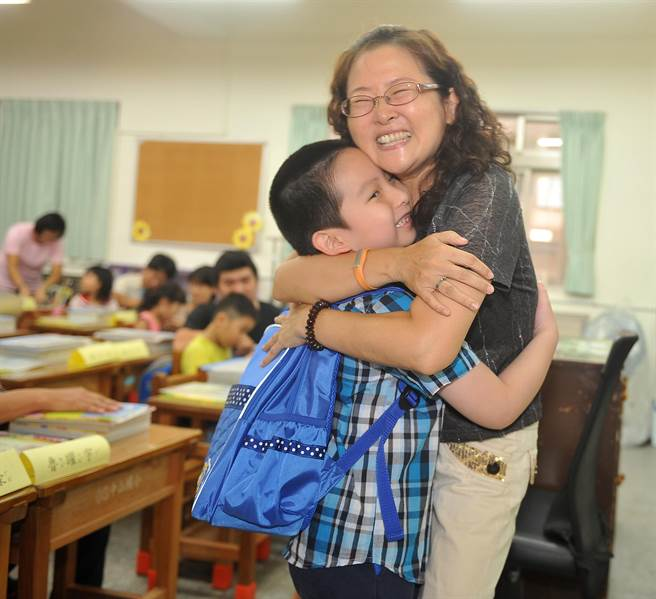 台北市中山國小老師楊桂芳(右)在教室歡迎小1新生們的加入,並用愛的抱抱,為小小新鮮人們啟動小學生活的新一頁。 (劉宗龍攝)