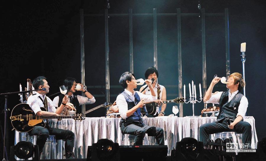 五月天28日在台上舉起滿裝「酸奶」的酒杯,阿信、冠佑、石頭彼此交杯敬19年兄弟情。(取材自臉書)