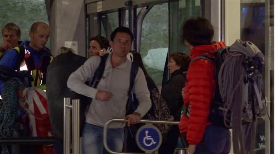 受困纜車脫困的乘客將被救援人員帶下山。(美聯社)